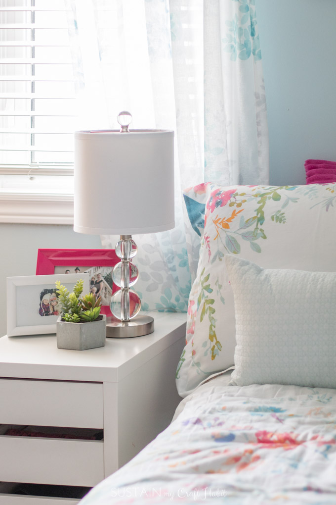 A crystal lamp with a white lampshade on a nightstand of a tween girl's bedroom