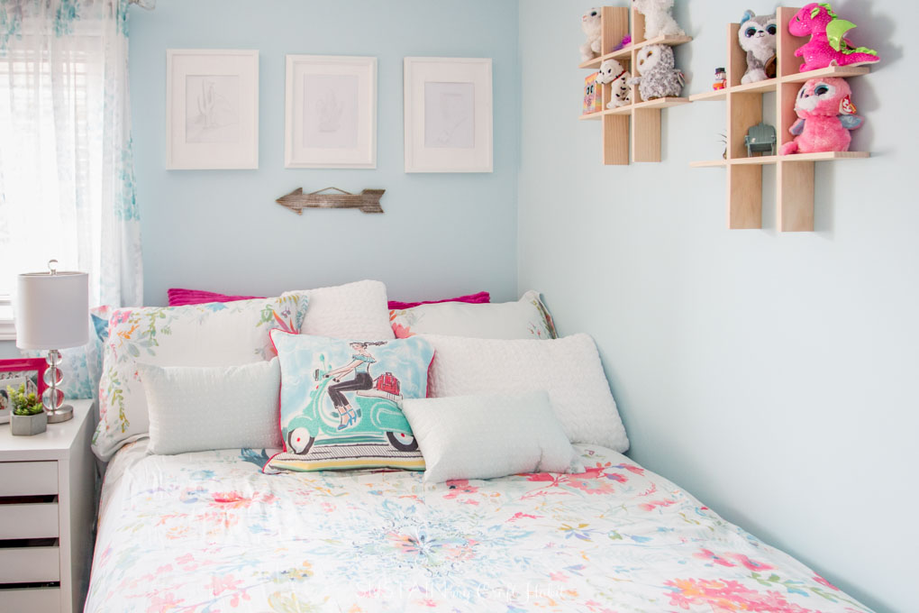 White, teal and pink throw pillows on a bed in a teal painted bedroom