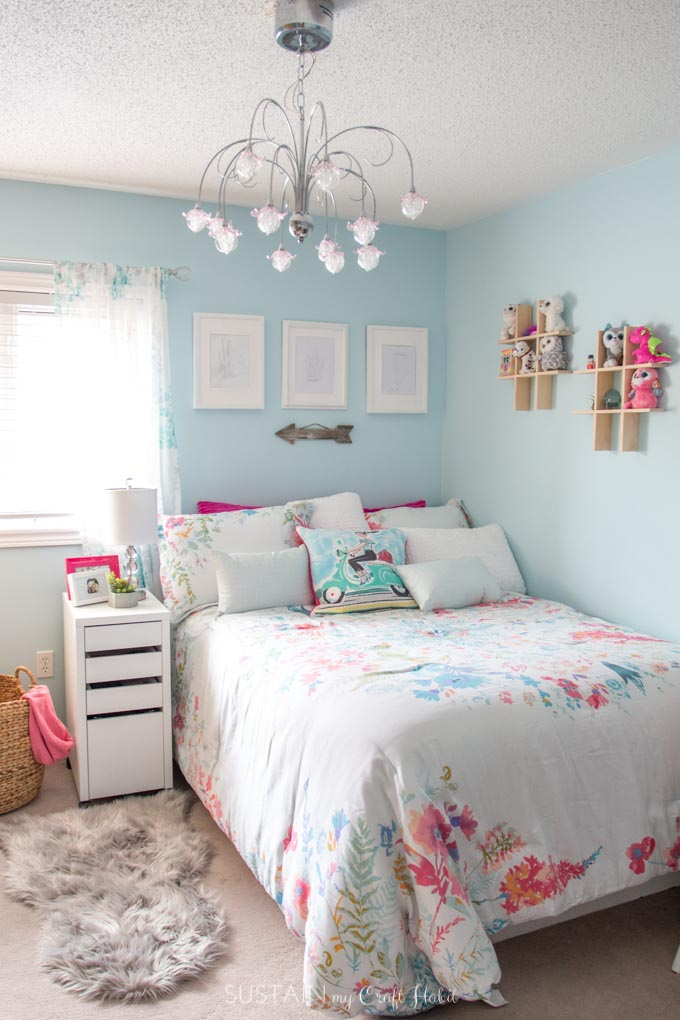 Bedroom with teal walls, chandelier and white and pink accessories