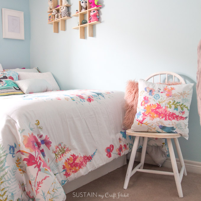 Wooden chair painted which with watercolor-inspired bedding in white, teals and pinks.