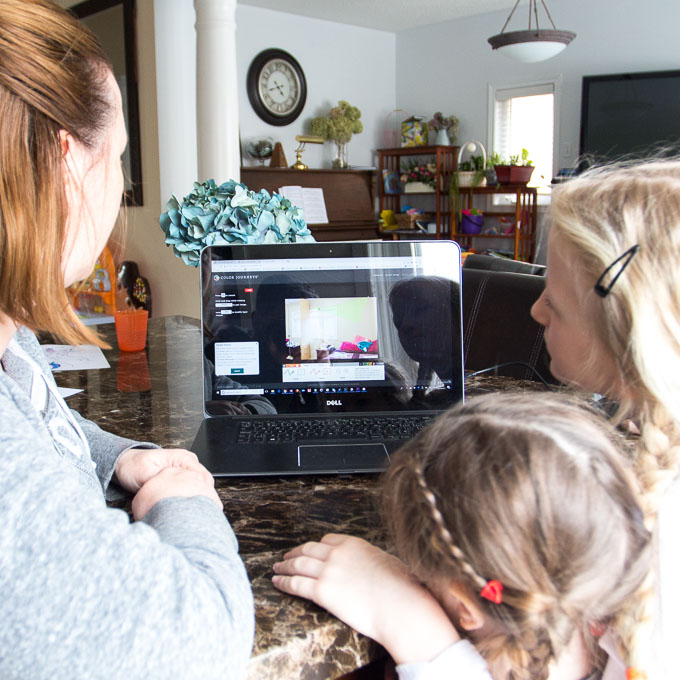 Woman and two children working at a kitchen table with a laptop