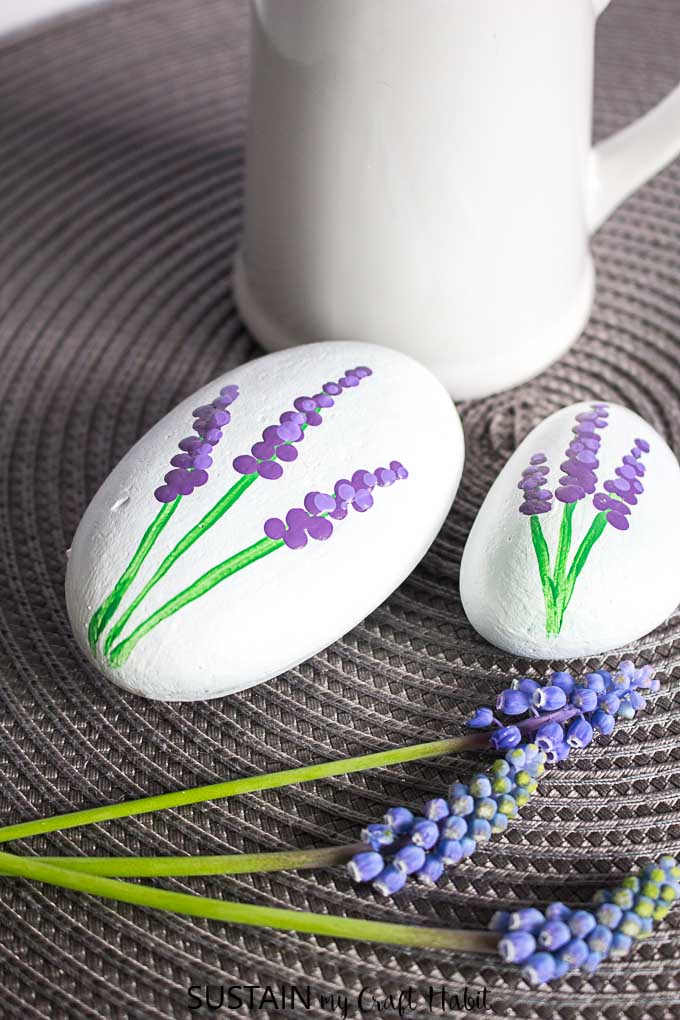 Oval stones painted white with purple grape hyacinths on a gray textured surface