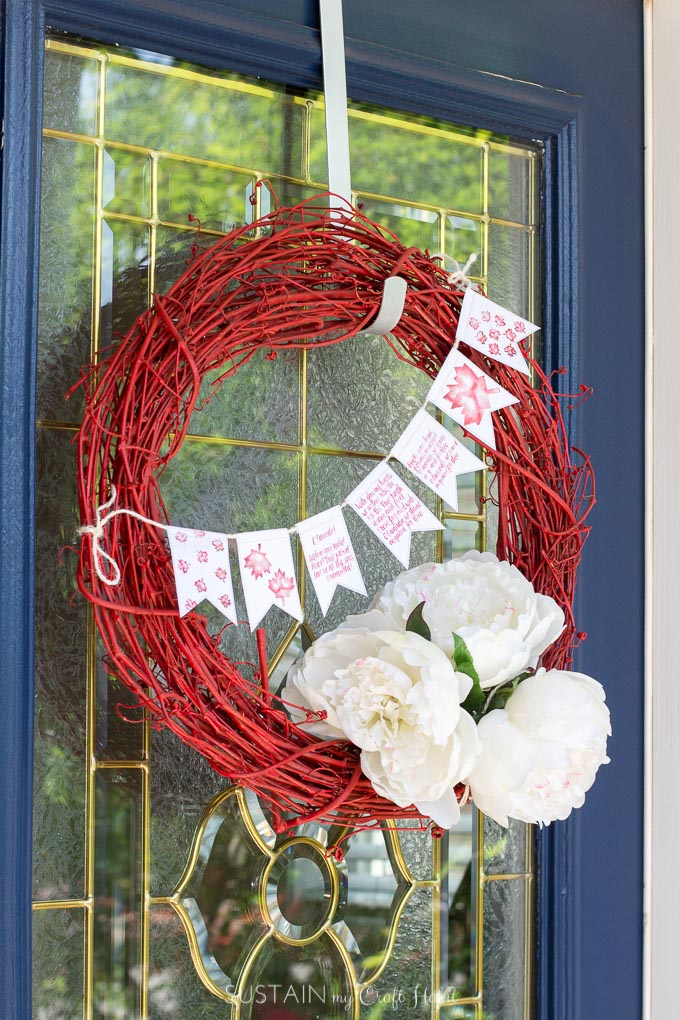 A red grapevine wreath decorated with white flowers and a small banner hanging on a blue painted front door