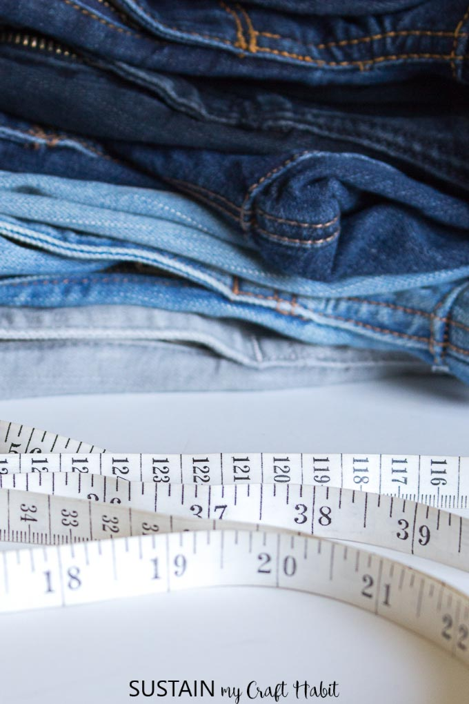 A stack of denim pants in different colors with a measuring tape in front.