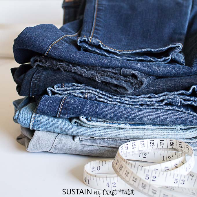 A stack of denim jeans of different colors on a white surface behind a measuring tape