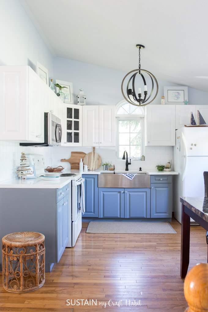 A Coastal Cottage Kitchen With High Ceilings, White And Gray Cabinets And  Dark Fixtures And