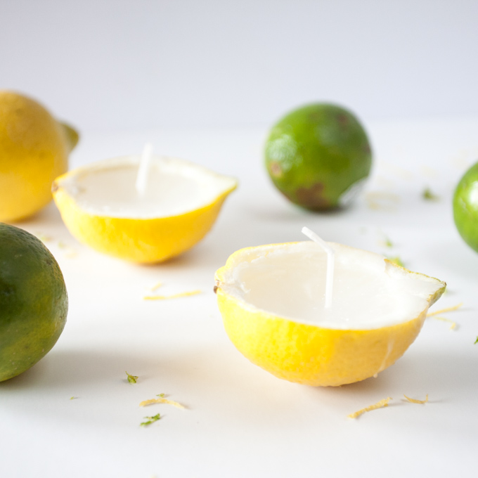 Two lemon rind candles surrounded by green limes on a white backdrop