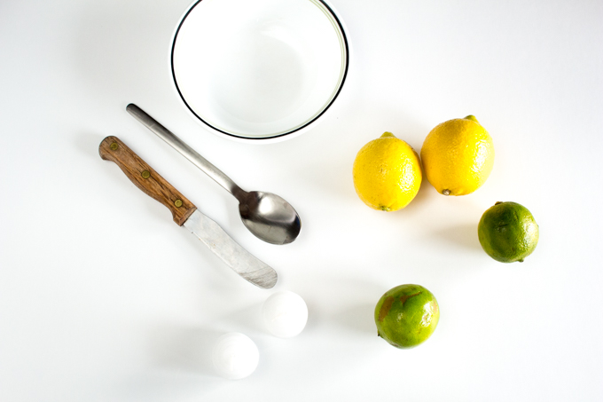Lemons, limes, paraffin candles, bowl, knife and spoon to make DIY citrus candles