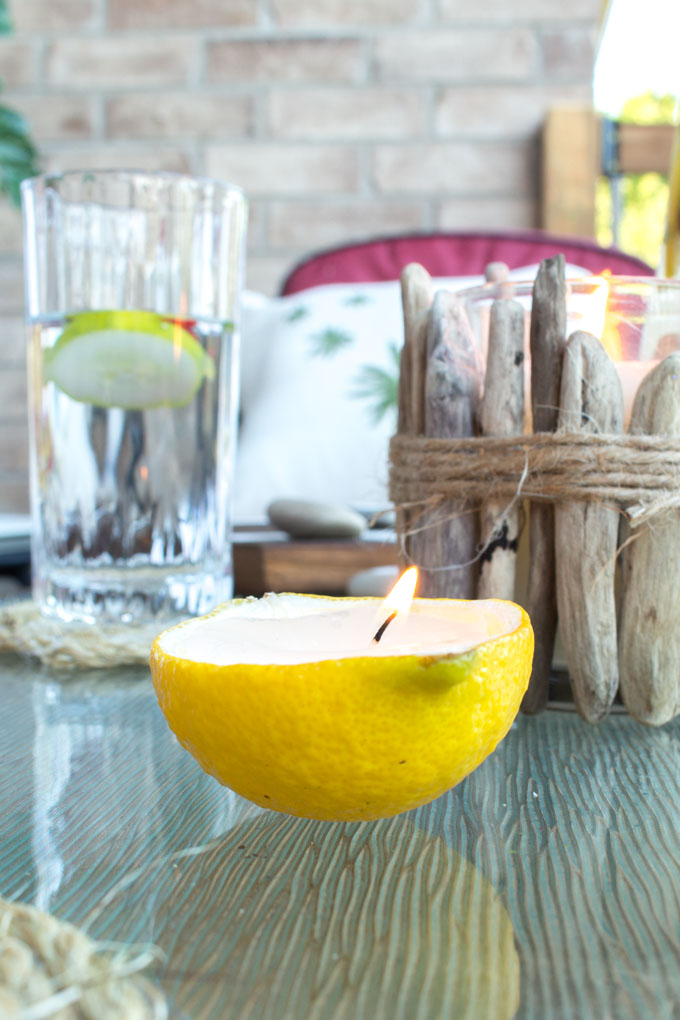 Lit candle made from a lemon rind on a glass outdoor patio table