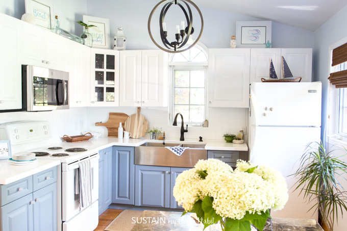 Entire view of a coastal style kitchen with white and gray painted cabinets decorated with touches of wood. A vase of white hydrangeas is in the foreground.