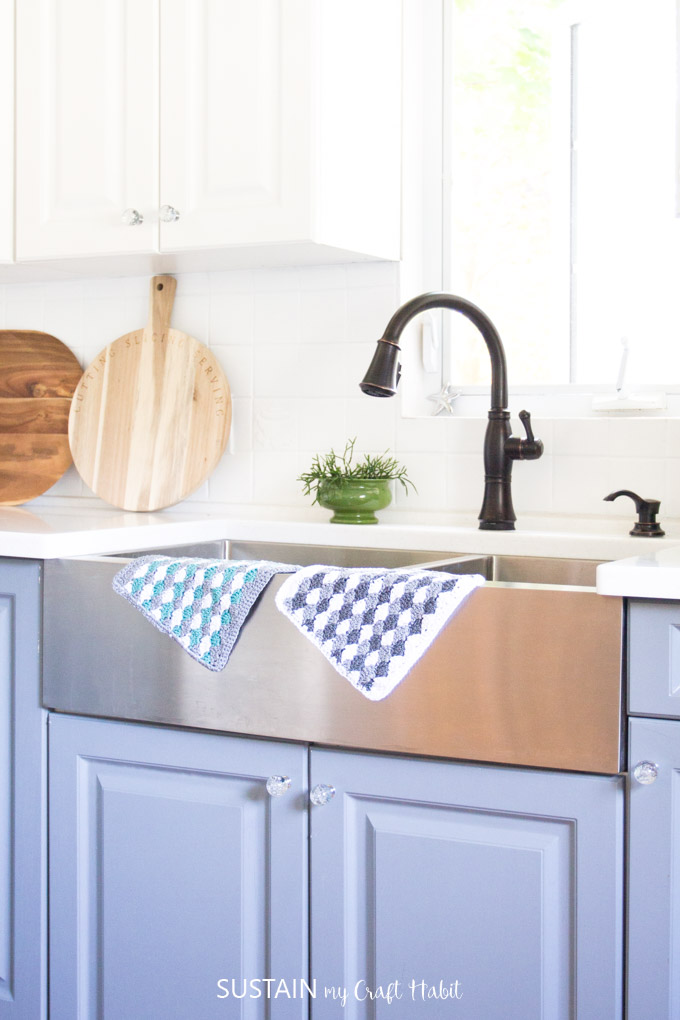 Two crochet dishcloths hanging over the edge of a farmhouse style sink.