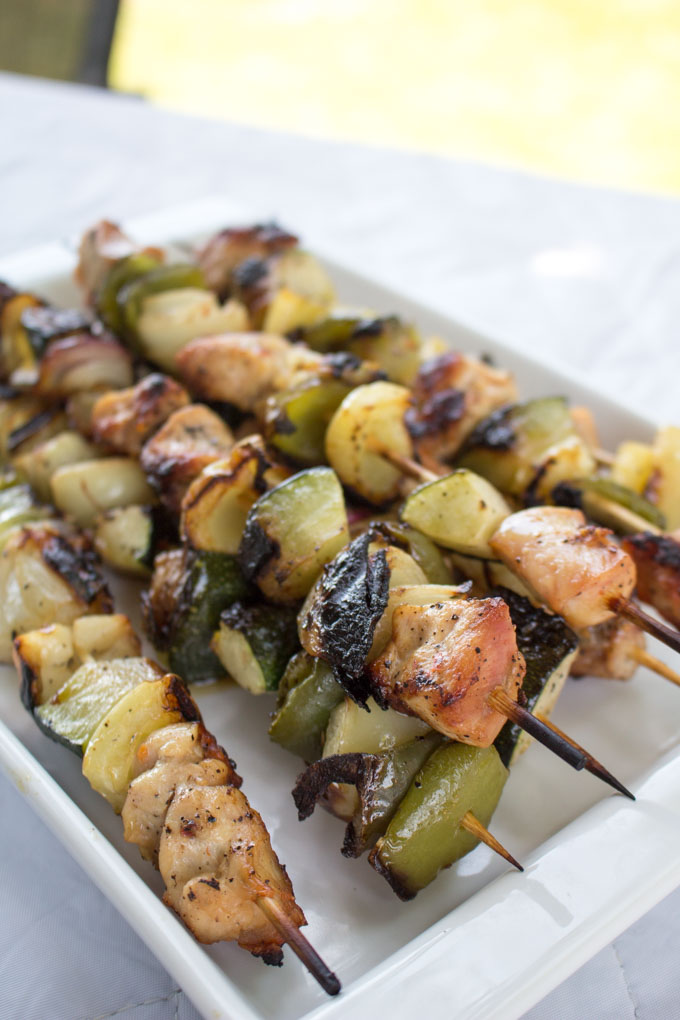 Platter filled with grilled chicken and veggie shish kabob skewers