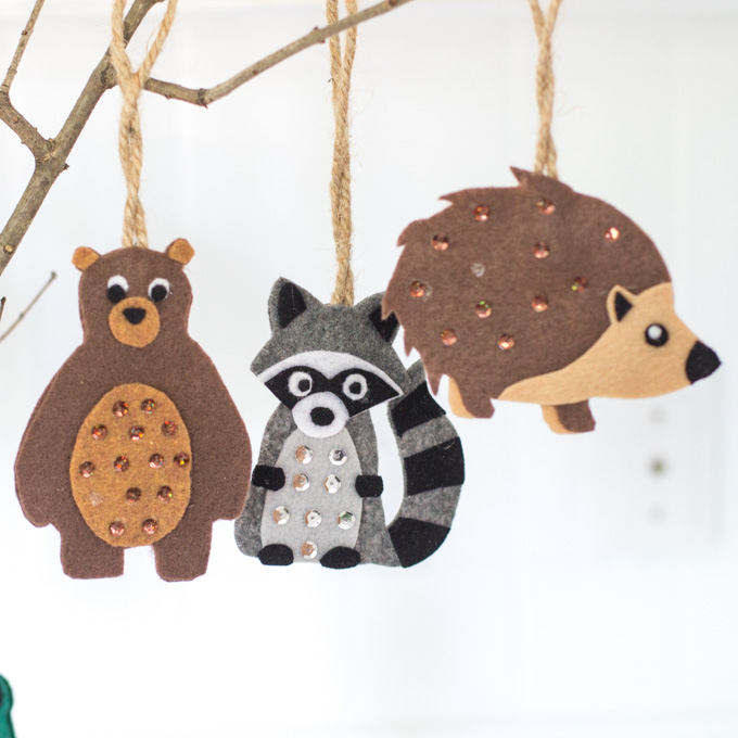 Small felt ornaments hanging from a branch as woodland baby shower decorations including a bear, raccoon and hedgehog