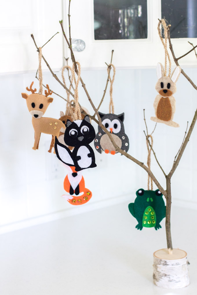 A set of felt ornaments hanging from a twiggy branch as woodland baby shower decorations
