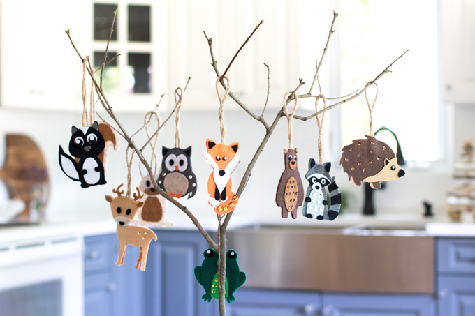 A small branch strung with woodland animal felt ornaments including a fox, owl, bear, racoon and more.
