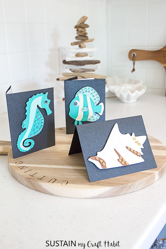 Set of coastal themed DIY cards on a kitchen counter including teal seahorse, fish and a white conch