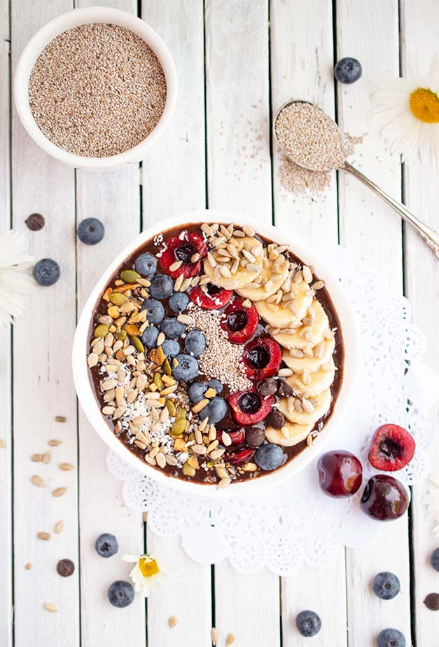 Delicious chocolate cherry smoothie bowl recipe topped with cherries, blueberries, seeds and sliced bananas on a white plank surface