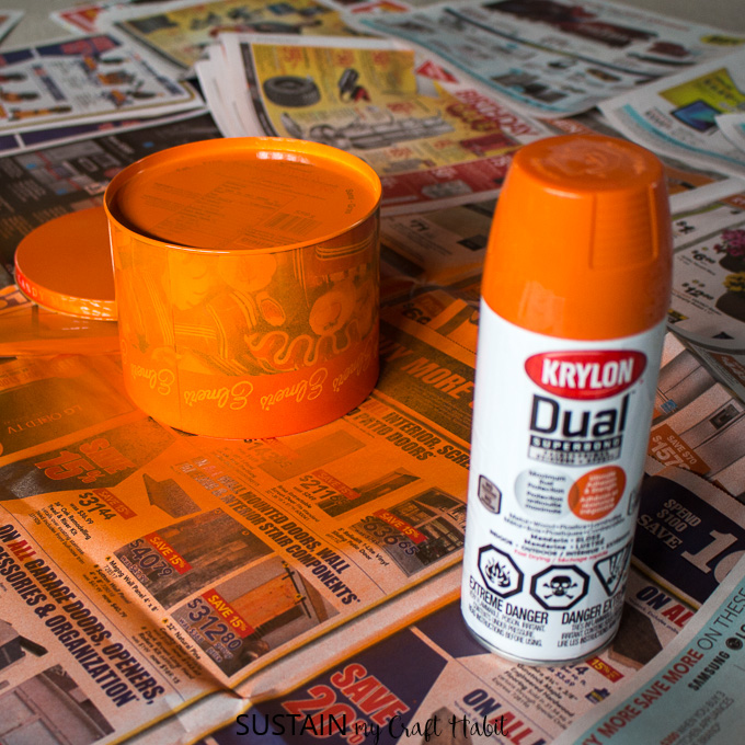Spray painting an old cookie tin with orange Krylon paint on a newspaper covered surface