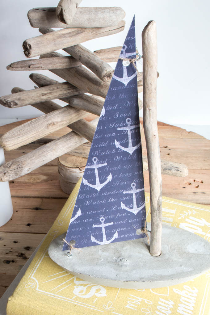 A decorative sailboat made with a concrete base, driftwood mast and nautical paper sail.