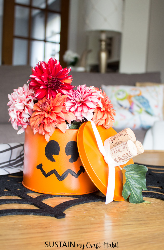 An old tin can, spray painted orange with a pumpkin face added on as an example of halloween decorating ideas