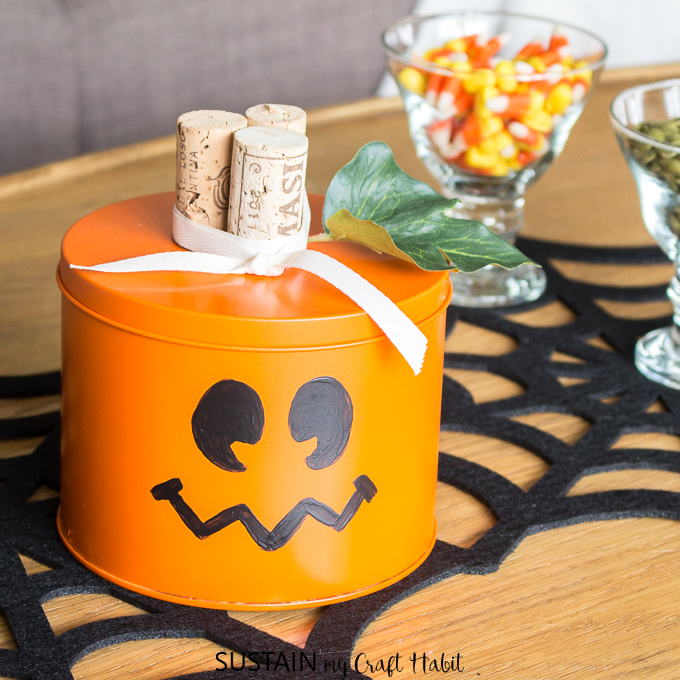 An adorable orange and black halloween pumpkin made from an upcycled cookie tin as a centerpiece on a coffee table