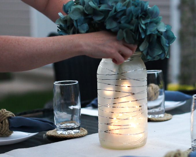 Placing faux florals into a frosted glass jar lantern