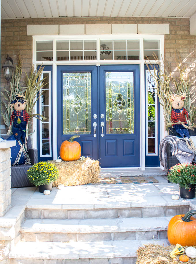 A fall front porch decorated with hay bales, orange pumpkins, mums, cornstalks and scarecrows