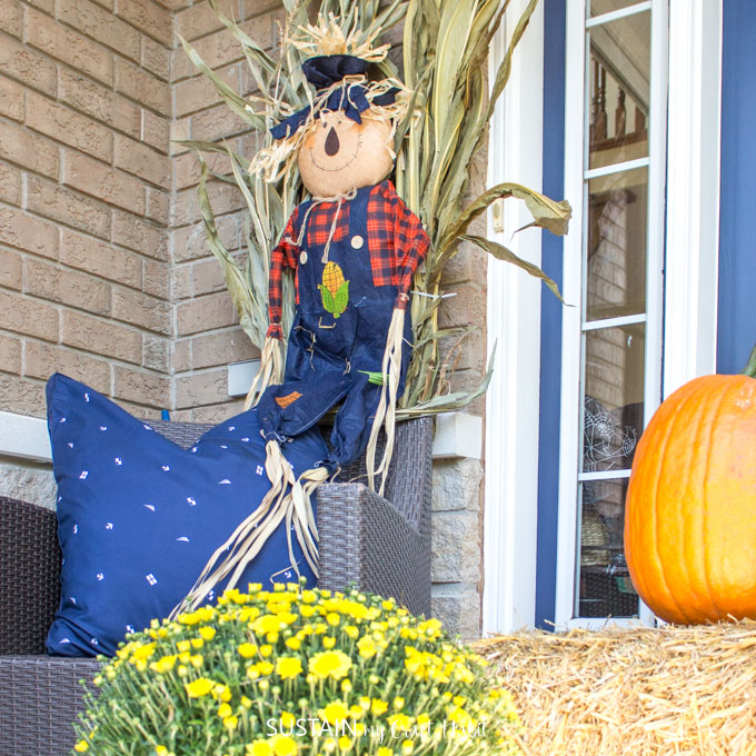 A scarecrow against cornstalks behind a chair on a fall front porch