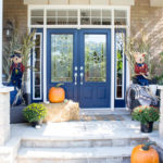 A front porch decorated for fall with orange pumpkins, hay, mums, scarecrows and cornstalks