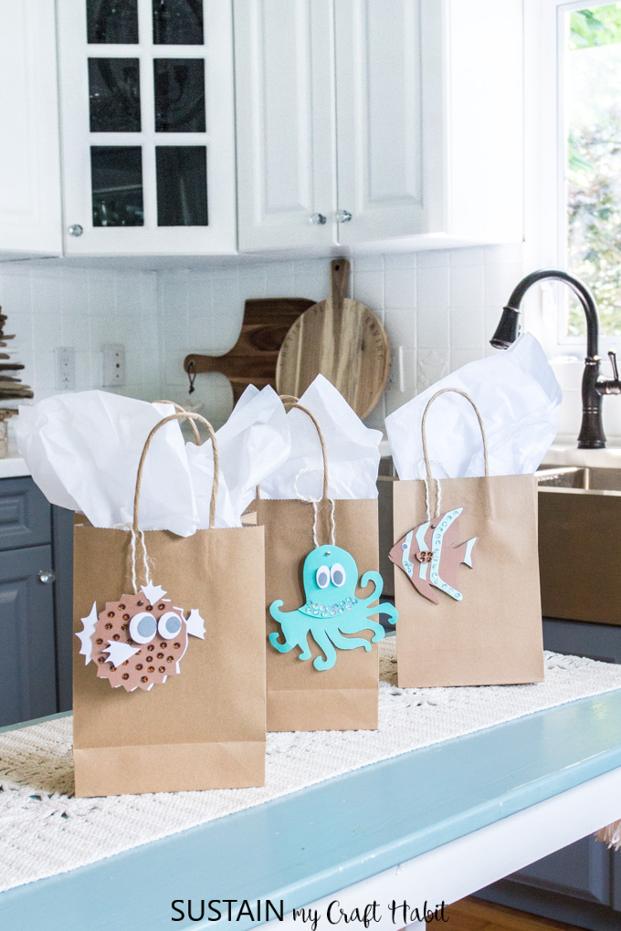 Set of three gift bags with white tissue paper and beachy printable gift tags including a puffer fish, octapus and clown fish