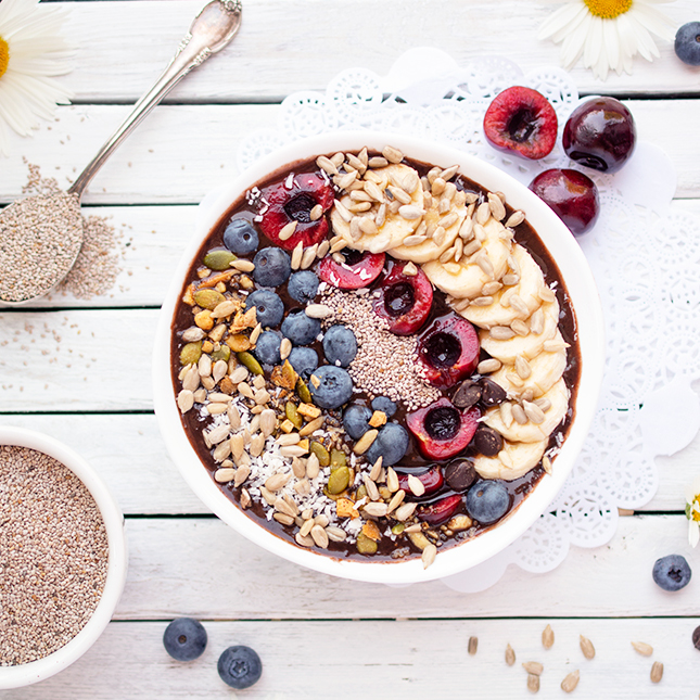 A wholesome bowl filled with cherry topped smoothie on a white plank background