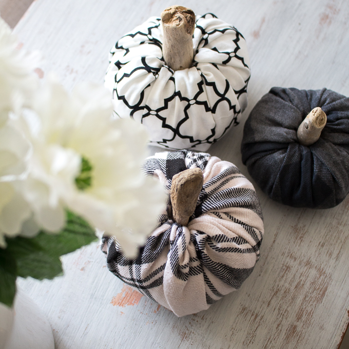 Overhead view of three fabric pumpkins of various sizes and patterns on a rustic wood surface.