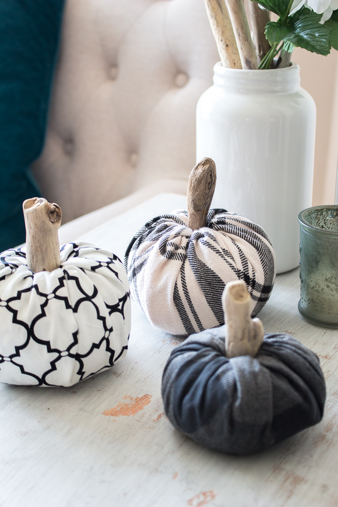 Three fabric pumpkins of different sizes make with scrap flannel and wood stems on a rustic wood surface. Neutral accessories surround the display.