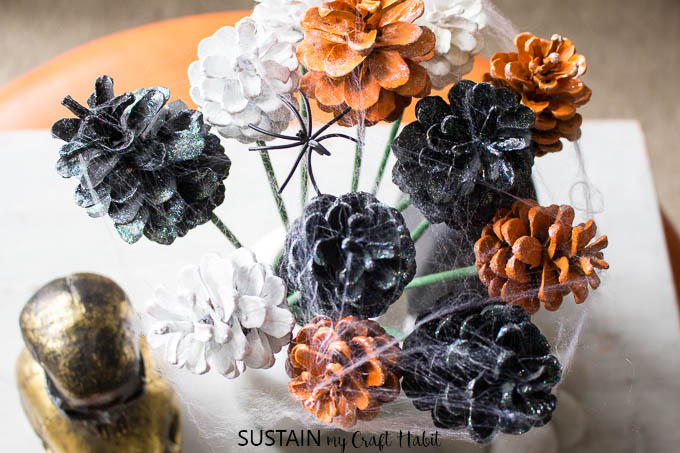 A view from above of black, gold and white painted pine cone flowers with faux spider webbing