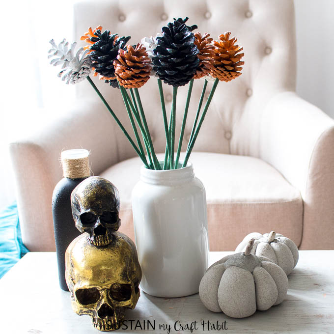 A bouquet of orangle, black and white painted pine cone flowers in a white vase surrounded by Halloween decor on a coffee table.