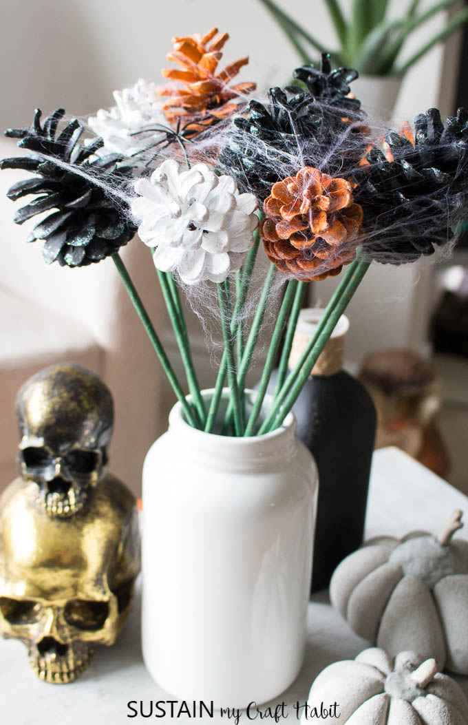A spooky Halloween vignette with orange, white and black painted pine cone flowers and other Halloween decorating elements.