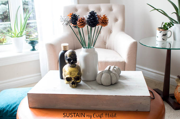 A vignette of orange, white and black pine cone flowers in a white glass vase surrounded by Halloween decorations