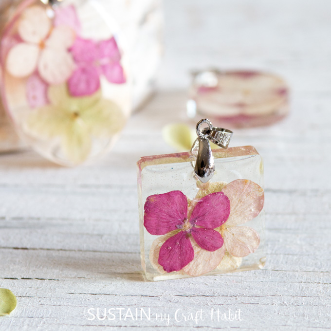 Close up image of a pressed pink hydrangea petals in a small square of clear resin. The pendant includes a silver bail for hanging onto a necklace.