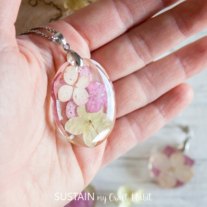 Woman holding an oval resin pendant with embedded hydrangea flowers