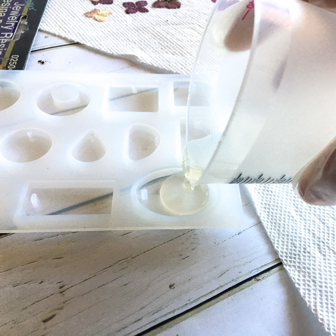 Pouring mixed resin solution into a silicone mold.