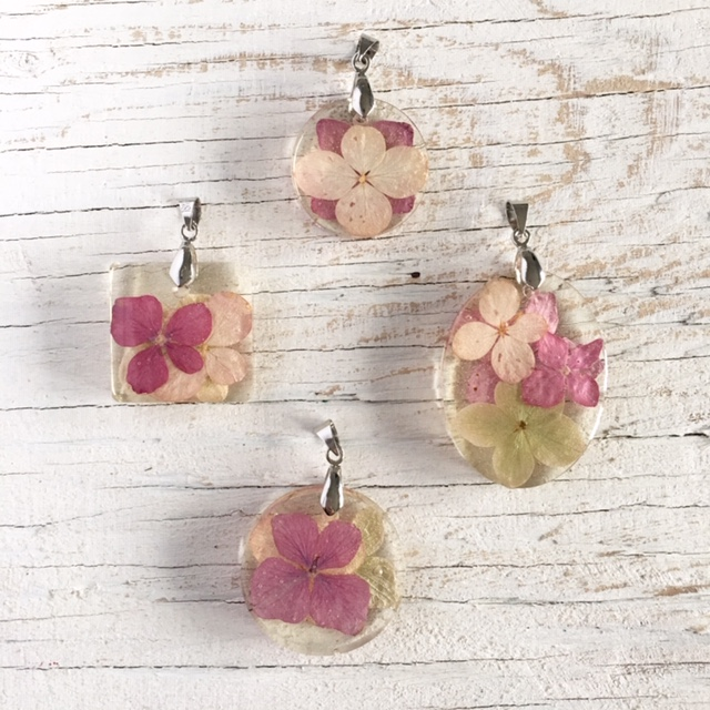 Overhead view of four completed resin pendants containing various colors and sizes of dried hydrangea flower petals. The pendants are arranged on a white wood surface.