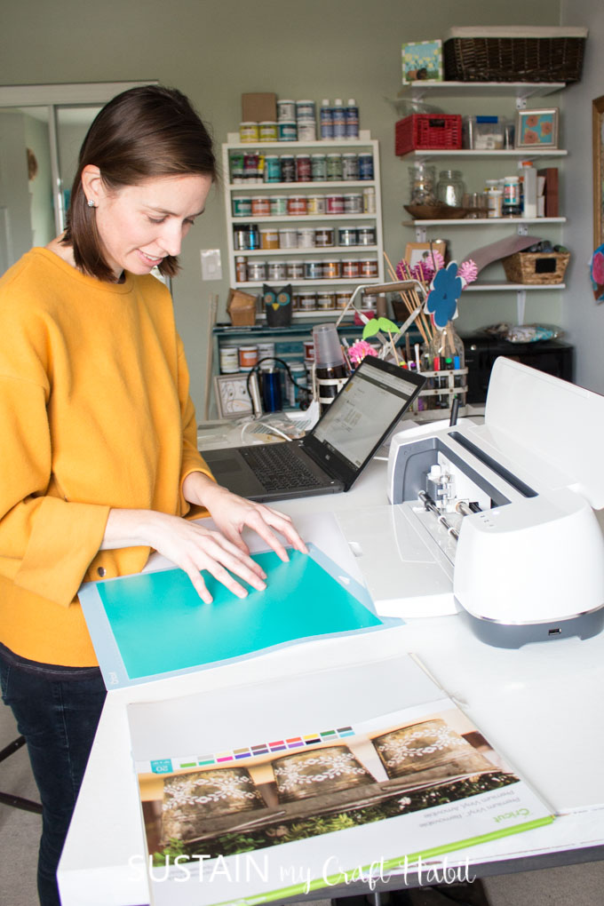 Sonya placing a sheet of turquoise vinyl onto a Cricut mat in preparation for feeding it into the Cricut Maker machine