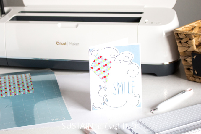A pretty greeting card with fabric embellishment on a table in front of a Cricut Maker machine