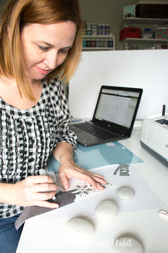 Jane using tweezers to pull black glitter vinyl from it's backing to reveal an intricate snowflake pattern cut by the Cricut Maker machine