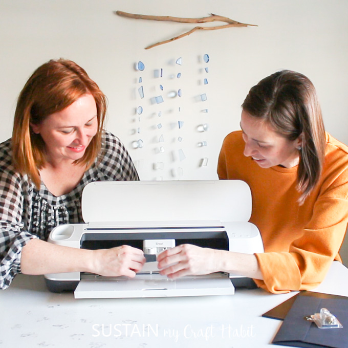 The post authors standing behind a Cricut Maker machine, looking at the mechanism inside.