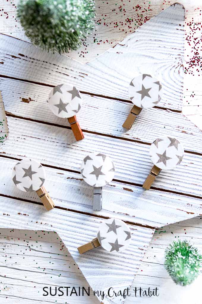 An arrangement of decorative clothespins, embellished with silver stars, laying on a rustic Christmas surface