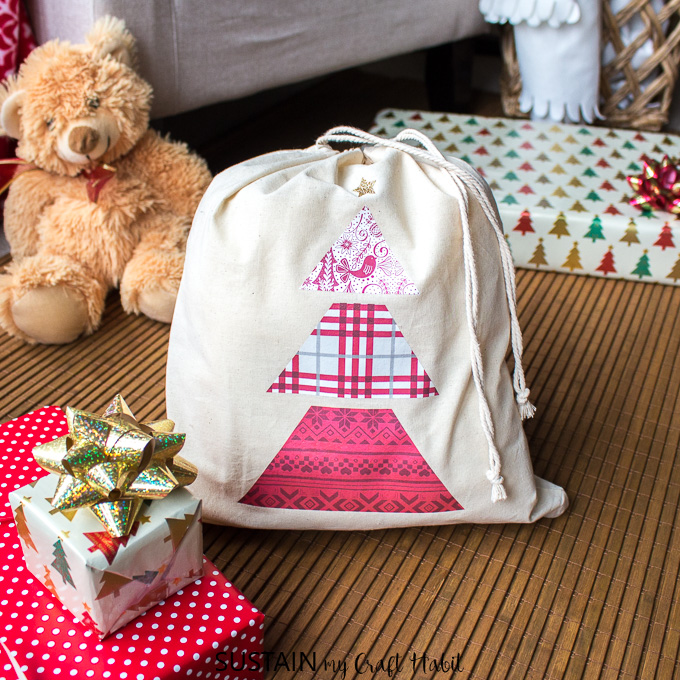 A reusable Christmas gift bag made with the Cricut EasyPress 2 and patterned heat transfer vinyl paper.
