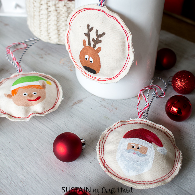 Sewing Christmas ornaments with canvas and hand-painted holiday motifs