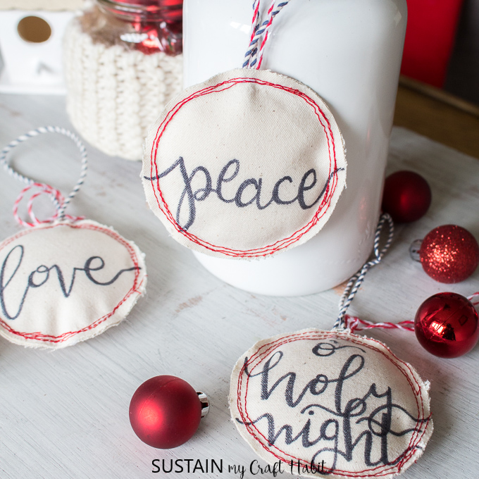 Three hand-lettered DIY Christmas ornaments on small canvases and gently stuffed