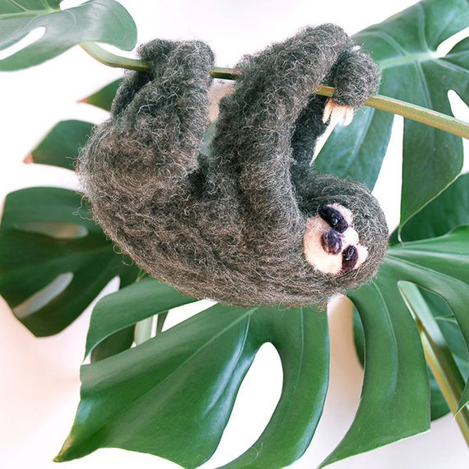 The cutest felted animal sloth hanging off of a monstera leaf shaft.